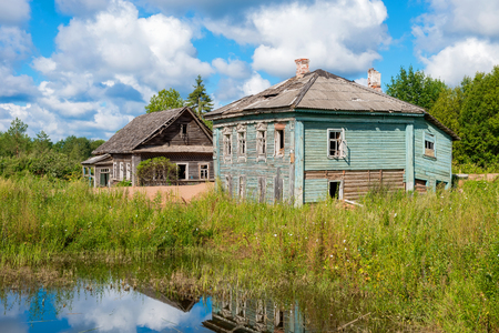 Evicted old wooden houses on the shore of muddy pond in the summer Editorial
