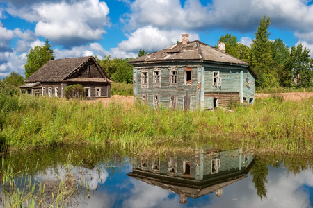 Evicted old wooden houses on the shore of muddy pond in the summer Stock Photo