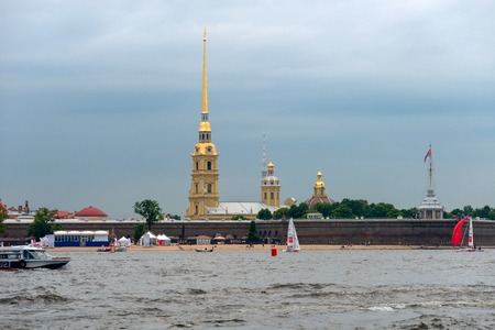 RUSSIA, SAINT PETERSBURG - AUGUST 18, 2017: View on the Peter and Paul Fortress, the river Neva, the steeple with a cross, dome, sky, warm summer day, storm sky Redakční