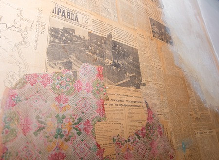 RUSSIA, SAINT PETERSBURG - AUGUST 18, 2017: Fragment of an old wall with ragged wallpaper and old communist newspapers