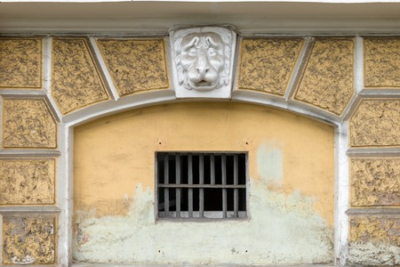 RUSSIA, SAINT PETERSBURG: Plaster head of a lion on the facade above a window with a lattice
