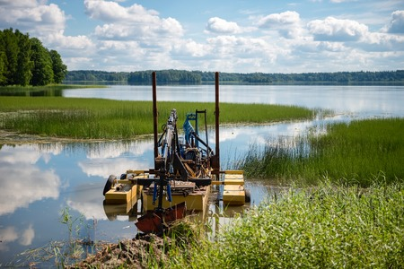 Cleaning the bottom of the lake with a dredge