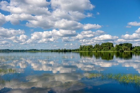 Lake Valday. Harmonious picture of a tranquil lake with reflections of trees and sky