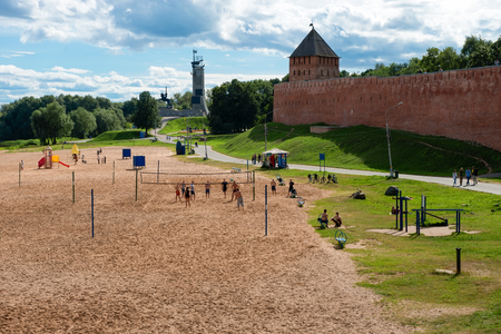 VELIKY NOVGOROD, RUSSIA - AUGUST 14, 2018: People playing volleyball on the beach of the river Vohov the walls of the Novgorod Kremlin