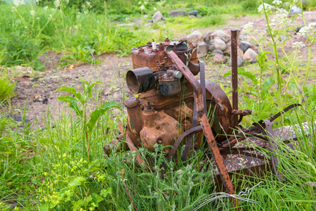 Old rusty car engine is standing on the street in the grass.