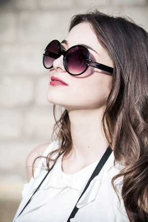 The girl in sunglasses against the wall  Looking at the sky Stock Photo