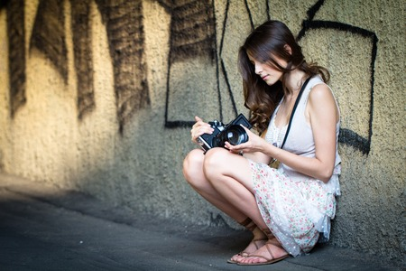 The girl with the camera sitting against the wall with graffiti Stock Photo