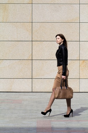 Business woman with a bag goes along business center