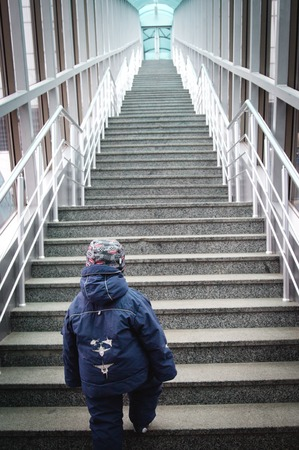boy makes the first steps up the stairs