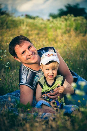 Boy and father on picnic in grass photo