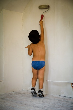 little boy paint wall in white color