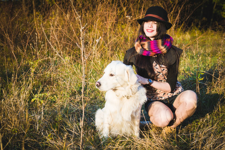 Girl in hat with dog in park have fun