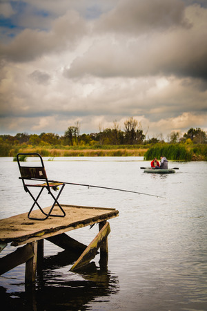 chair on the dock with a fishing rod lake