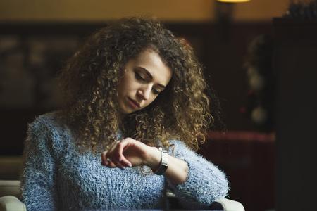 punctuality: Una mujer joven y hermosa que espera en caf� y ver el reloj