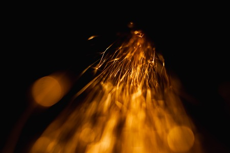 Bokeh lights on black background, shot of flying fire sparks in the air Stock Photo