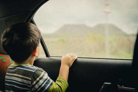 Little boy looking through window. He travels on a car