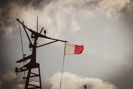 pilot flag on a mast on a background of the cloudy sky