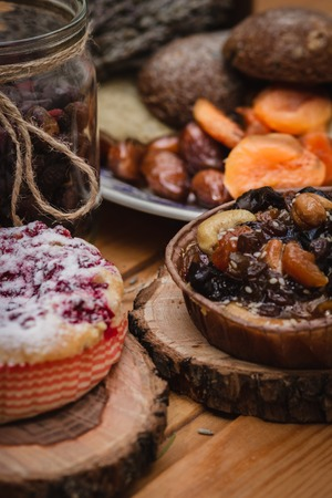 pie on wooden saucer on a background of dried fruit and jars with berries