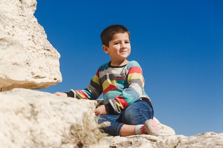 boy sits on the top of rock and look down to Valley