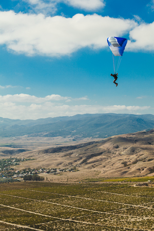 paraglider flying above the valley with mountains