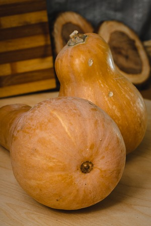 Two pumpkins on wooden table. front view