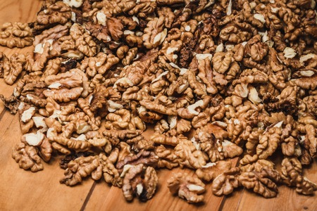Closeup of big shelled walnuts pile background on wooden table