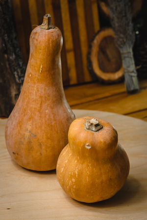 two pumpkins on a wooden cutting board on a background of kitchen utensils Stock Photo