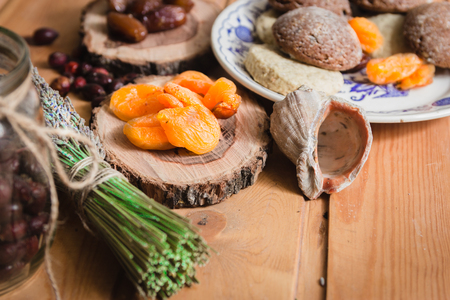 the composition of the traditional winter ingredients - dried fruits, pastries, rosehip seed tea, bundle of lavender and shell Stock Photo