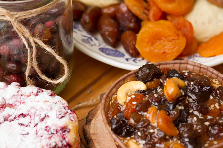 blueberry pie and pecan pie on wooden saucer on a background of dried fruit and jars with berries