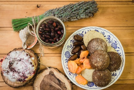 top composition of plate with dried fruits and cakes on wooden saucers Stock Photo