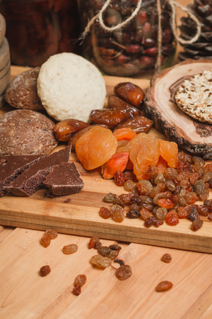 chocolate, dried apricots, and homemade cookies on a wooden board Stock Photo