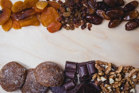 Composition of dried fruit, nuts, chocolate and home-made cakes on the wooden table,