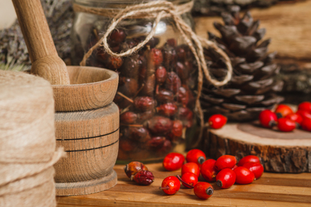 Dried and fresh berries wild rose on a background of  wooden table Stock Photo