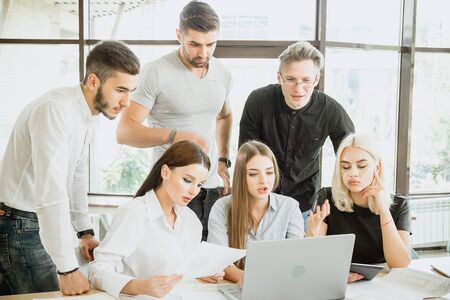 Team of young people in work process in front of laptop Stock Photo