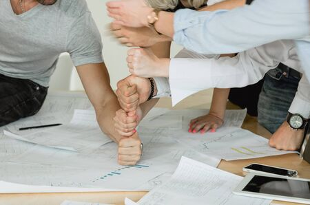 Corporate training employees build a pyramid of fists on the table On the table are pen drawings of tablets and telephones Stock Photo