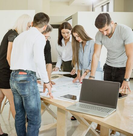 Urgent meeting in the office Team of young people clean up the documents Stock Photo