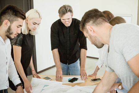 Hard work on the project. All employees and the project manager are standing above the table with documents discussing the project. Stock Photo