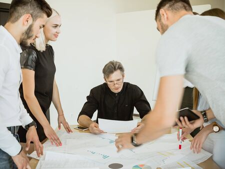 The company of young employees at a meeting with the project manager offer their options for project implementation Stock Photo