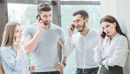 Four young employees Two men and two women employees communicate in a casual conversation Business conversation