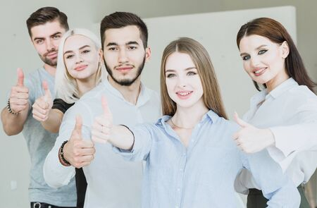 Team of young people making thumbs up in a bright room Stock Photo