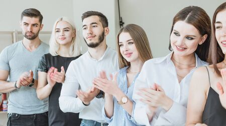 Young team applauding while standing in the office