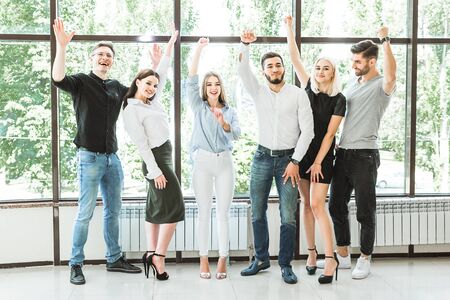 Portrait of six attractive and positive people that is having fun raising hands up bright at vivid trees and office windows background