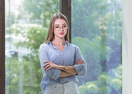 Thoughtful young lady with glasses in blue shirt is thinking about and dreaming. She crosses her arms over chest. Occupation concept
