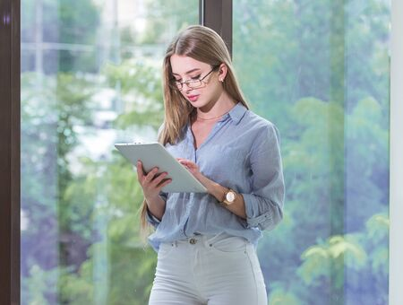 Beautiful young female employee with a tablet computer in her hands working in a spacious bright office Stock Photo