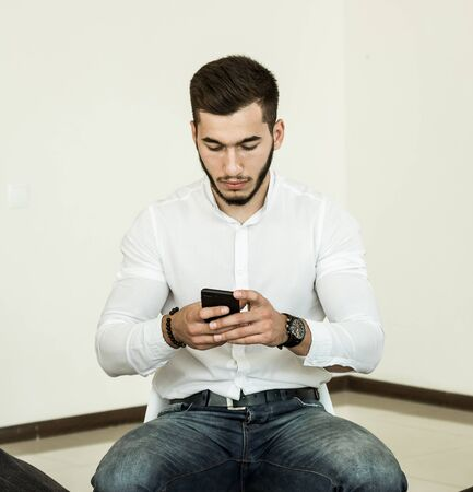 A young man with a beard in a white shirt works with a smartphone while sitting on a chair in a bright room