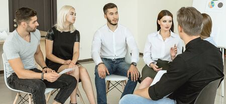 Young university students having a group discussion sitting together on a circle of chairs smiling and talking with a chalkboard visible behind Stock Photo