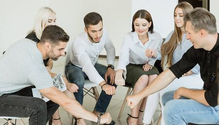 Diverse people sitting in circle spread hands at group therapy session, team practice together for cooperation give psychological support, counseling training society concept