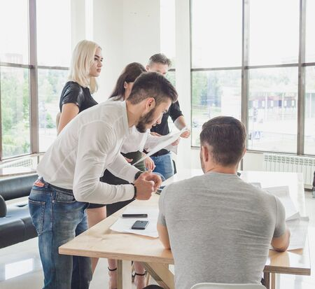 The young employee offers his own solution to the boss while the rest of the team is working Stock Photo