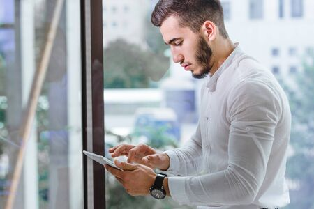 Cropped closeup of young arab ethnency man using tablet pc indoor Stock Photo