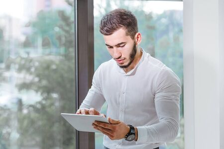 closeup of young arab ethnency man using tablet pc indoor Stock Photo